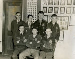 Harold Garver with six F.F.A. boys in front of a F.F.A. display on a wall in the Shawnee Mission...